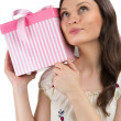Young woman puts her ear to the present wrapped in red paper, is — Stock Photo