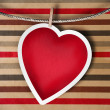 Stock Photo: Valentine background: heart hanging on clothespin