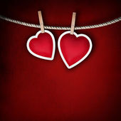 Paper hearts hanging on a rope on grunge background — Stock Photo