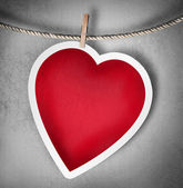 Paper heart hanging on a rope on grunge background — Stock Photo
