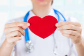 Female doctor with stethoscope holding red human heart — Stock Photo