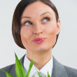 Adult business woman looking up and holding lucky bamboo plant s — Stock Photo