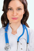 Closeup portrait of adult female doctor with kind look at hospit — Stock Photo