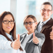 Successful young business showing thumbs up sign - Stock Photo