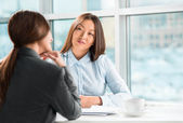 Two business women talking and signing contract at office — Foto de Stock