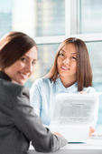 Two business women talking and signing contract at office — Stock Photo