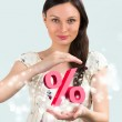 Portrait of young girl holding discount symbol in her arms — Stock Photo