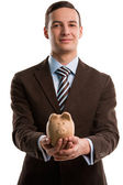 Young happy business man holding piggybank over white background — Stock Photo