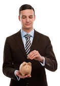 Young happy business man putting money in the piggybank — Stock Photo