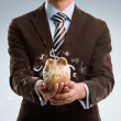 Stock Photo: Business man holding piggy bank, currency symbols flying around