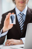 Detail shot - business man showing business card with idea symbo — Stock Photo