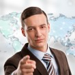 Stock Photo: Portrait of young man standing in front of big world map