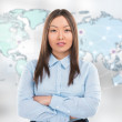Portrait of young woman standing in front of big world map — Stock Photo