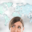 Portrait of young woman standing in front of big world map. — Stock Photo