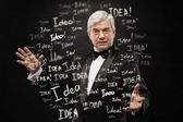 Idea concept. Mature business man standing on black background — Stock Photo