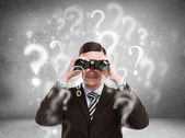 Handsome business man with binoculars and question marks — Stok fotoğraf