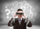 Hombre de negocios guapo con binoculares y signos de interrogación — Foto de Stock