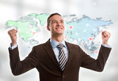 Portrait of young man standing in front of big world map. — Stock Photo