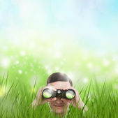 Man looking through binoculars from grass — Stock Photo
