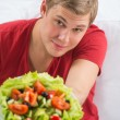 Young handsome man preparing to eat fresh healthy salad - Stock Photo