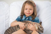 Cute little girl hugging tabby cat with love, looking at camera. — Stock Photo