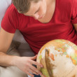 Portrait of young handsome caucasian man at home looking at globe — Stock Photo #23114402