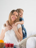 An adorable young girl hugging her mother's neck from behind — Stock Photo