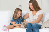 Mother and daughter sitting on sofa and cuddling cat — Stock Photo