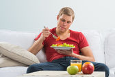 Young man eating vegetarian salad with appetite — ストック写真