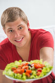Young man eating vegetarian salad with appetite — Stock Photo