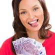 Woman holding up fanned out banknotes - Stockfoto