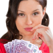 A pretty young woman holding a fan of euro bills — Stock Photo