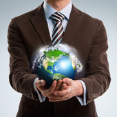 Businessman keeps the world in his hands — Stock Photo