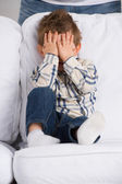 Portrait of little boy closing eyes with his hands at home — Stock Photo