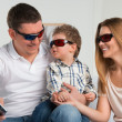 Family laughing while watching television together in the living-room wearing 3d glasses — Stock Photo