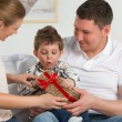 Couple giving gift to their little son in the living room. — Stock Photo