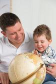 父亲和儿子看着地球在家里,很开心 — 图库照片