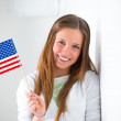 Portrait of a lovely young woman with United State's flag smiling — Stock Photo #24978619