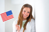 Portrait of a lovely young woman with United State's flag smiling — Stock Photo