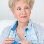 Senior woman knitting on her sofa at home — Stock Photo