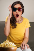 Shocked young woman watching 3D movie — Stock Photo