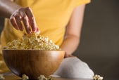 Unrecognizable woman eating popcorn at the cinema — Stock Photo