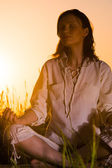 Beautiful Yoga woman siting against sunrise — ストック写真