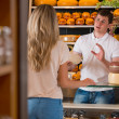 Male salesman in cheese store with a female customer — Stockfoto