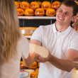 Male salesman in cheese store with a female customer — Stock Photo #28611593