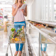 Young woman shopping at supermarket. Holding shopping list and thinking what she should buy next — Stock Photo