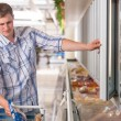 Man in a supermarket standing in front of the freezer — Stock Photo