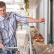 Stock Photo: Min supermarket standing in front of freezer