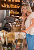 Positive young woman at the bakery store choosing what she wants to by and placing order to seller — Stock Photo