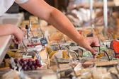 Unrecognizable male supermarket worker with cheese closeup — Stock Photo